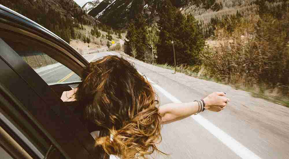 woman in passenger seat of car on a road trip