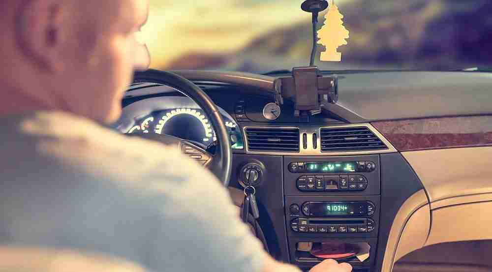 man looking at air conditioning controls on car dashboard